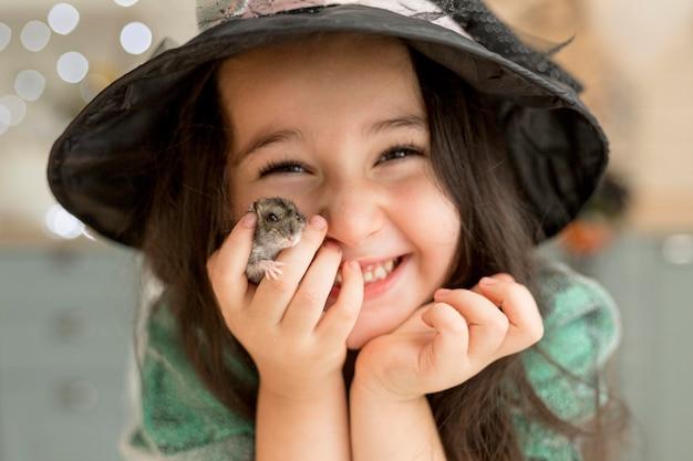Крупным планом милая маленькая девочка держит хомяка Бесплатные Фотографии