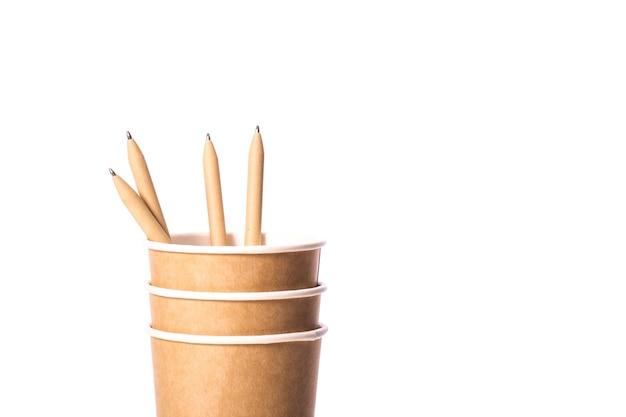 Закройте вверх по взгляду одноразовых коричневых бумажных стаканчиков с экологически чистыми органическими многоразовыми ручками, изолированными на белом фоне. экология, природные биоразлагаемые материалы, концепция утилизации. копировать текстовое пространство Premium Фотографии