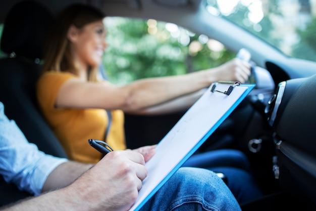 バックグラウンドで女性学生のステアリングと車の運転中にチェックリストを保持しているドライビングインストラクターの拡大図 無料写真