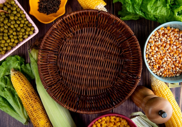 木製のテーブルにトウモロコシトウモロコシ種子グリーンピース黒コショウで空のバスケットのクローズアップビュー 無料写真
