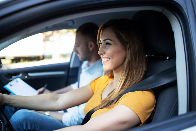 車を運転している女子学生とチェックリストを保持しているインストラクターのクローズアップビュー 無料写真