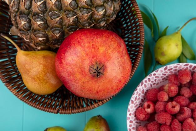 バスケットのパイナップルザクロ桃と桃と青の表面にラズベリーのボウルとして果物のクローズアップ表示 無料写真