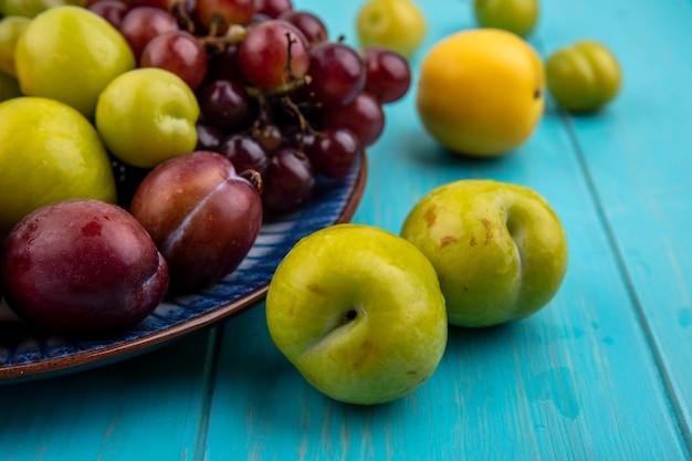 プレートと青い背景のプルオットネクタコットプラムとブドウとしての果物の拡大図 無料写真