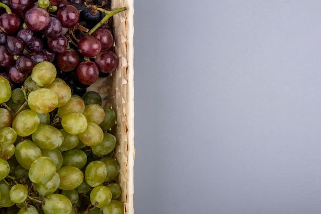コピースペースと灰色の背景にバスケットのブドウの拡大図 無料写真