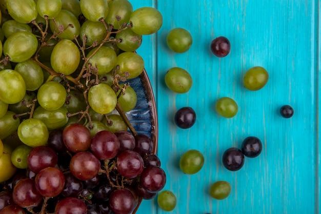 プレートのブドウと青い背景のブドウの果実のパターンの拡大図 無料写真