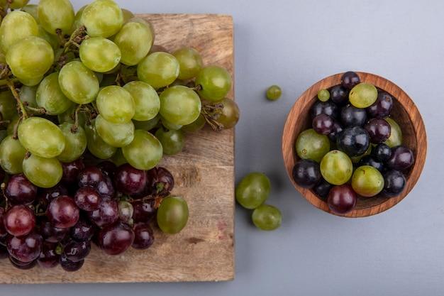 まな板の上のブドウと灰色の背景の上のブドウの果実のボウルの拡大図 無料写真