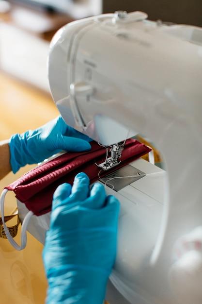 Крупным планом вид рук шитья тканевая маска для лица с швейной машиной Бесплатные Фотографии