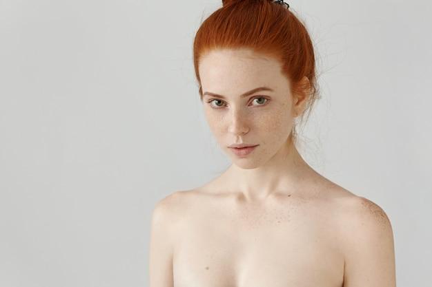 そばかすのある驚くべき赤毛の若い女性の頭と肩のクローズアップ表示 無料写真