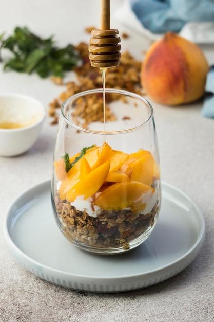 Крупным планом вид мюсли с персиками в стекле Бесплатные Фотографии