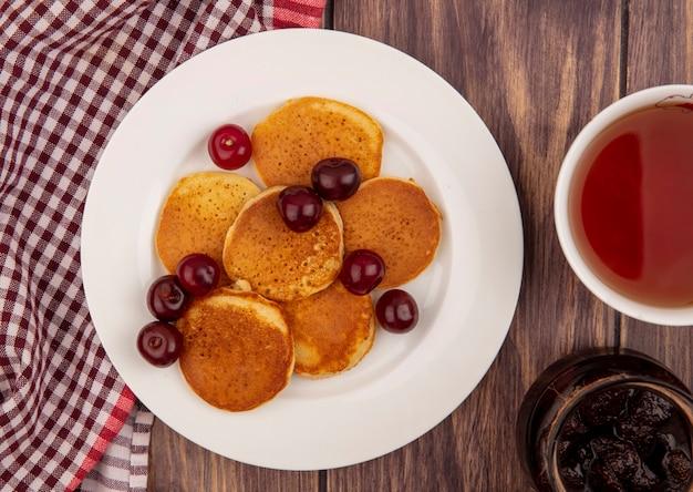 Крупным планом - блины с вишней в тарелке на клетчатой ткани с чашкой чая и клубничным вареньем на деревянном фоне Бесплатные Фотографии
