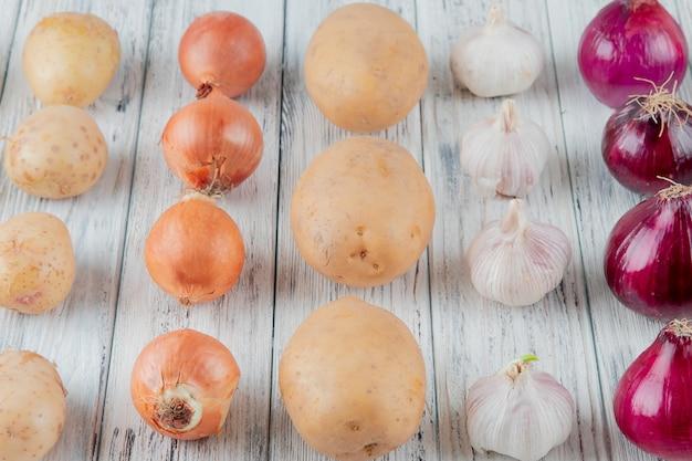Закройте вверх по взгляду картины овощей как чеснок картошки лука на деревянной предпосылке Бесплатные Фотографии