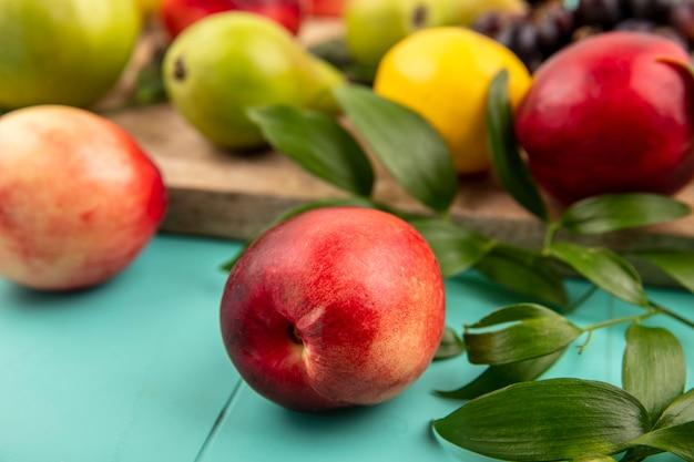 青い背景のまな板に葉と梨レモンと桃の拡大図 無料写真