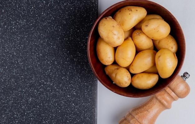 Крупным планом вид картофеля в миску с солью и разделочную доску на белом столе Бесплатные Фотографии