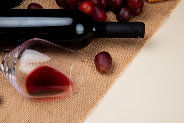 白い背景の荒布を着た赤ワインとブドウのクローズアップビュー 無料写真