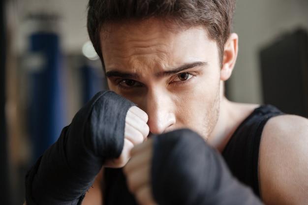 ジムで運動をしている深刻なボクサーのクローズアップ表示 無料写真