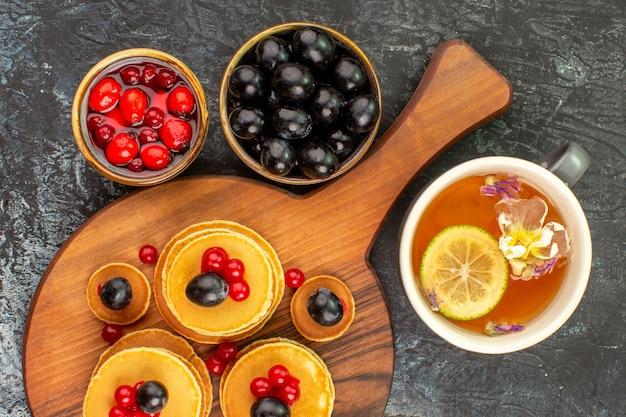 フルーツとレモンのお茶を添えた蒸れたパンケーキのクローズアップビュー 無料写真
