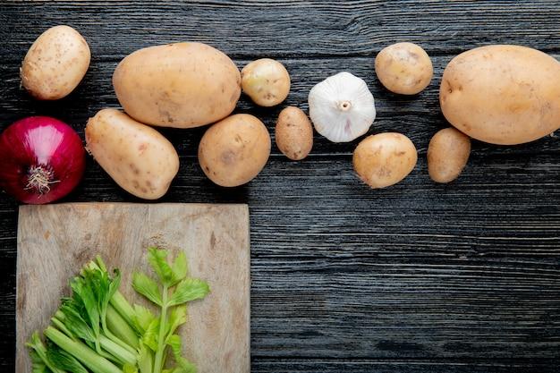 コピースペースを持つ木製の背景にまな板の上のカットセロリと玉ねぎジャガイモニンニクとして野菜のクローズアップ表示 無料写真