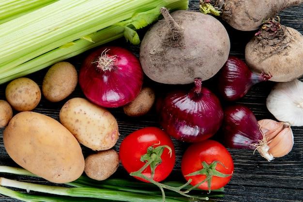 木製の背景にジャガイモセロリビートルートタマネギトマトなどとして野菜のクローズアップ表示 無料写真