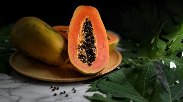 Крупным планом вид всей и наполовину сладкой папайи на деревянной тарелке Premium Фотографии