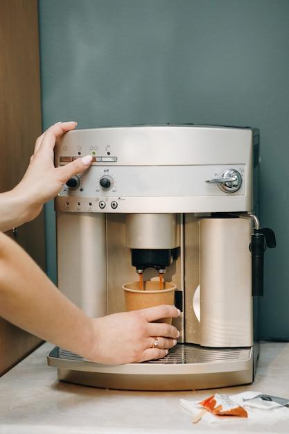 Взгляд конца-вверх рук женщины заваривая чашку кофе Premium Фотографии