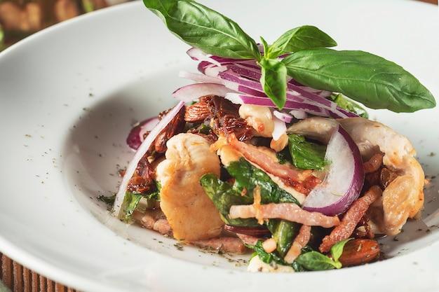 Panzanella 또는 Panmolle- 담근 된 부패한 빵, 양파, 토마토 나무 배경에 Inwhite 그릇의 인기있는 이탈리아 다진 된 샐러드에 뷰를 닫습니다. 프리미엄 사진