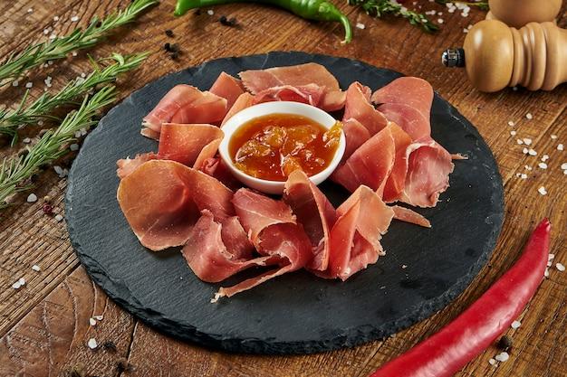 Закройте вверх по взгляду на закуске jamon serrano с сладостным соусом на черной плите на деревянной поверхности. antipasti Premium Фотографии