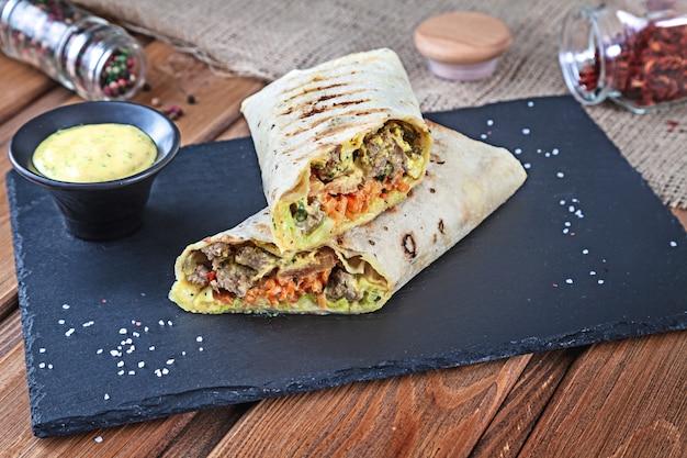 Закройте вверх по взгляду на сандвиче shawarma, крене гироскопа свежем в lavash. шаурма служил на черном камне. кебаб в лаваше с копией пространства. традиционная ближневосточная закуска, фаст-фуд. горизонтальный крупным планом Premium Фотографии