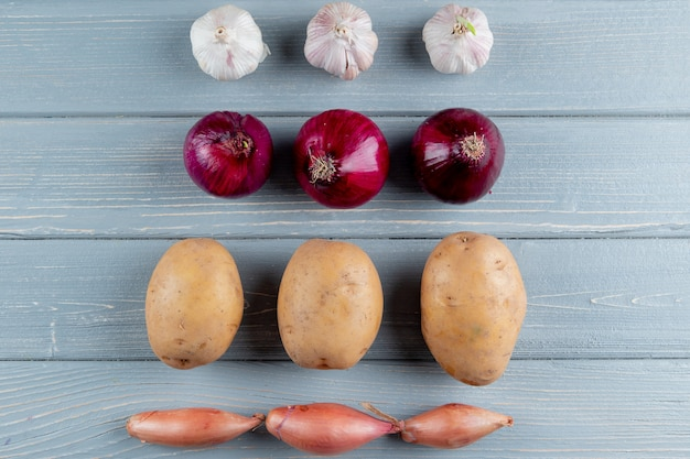 Close up view of pattern of vegetables as garlic onion potato shallot on wooden background with copy space Free Photo