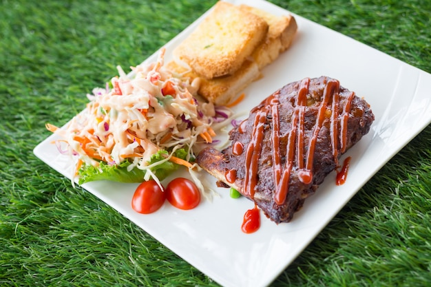 Close up view of pork barbecue ribs with barbecue sauce that served with garlic bread and vegetable salad. Premium Photo
