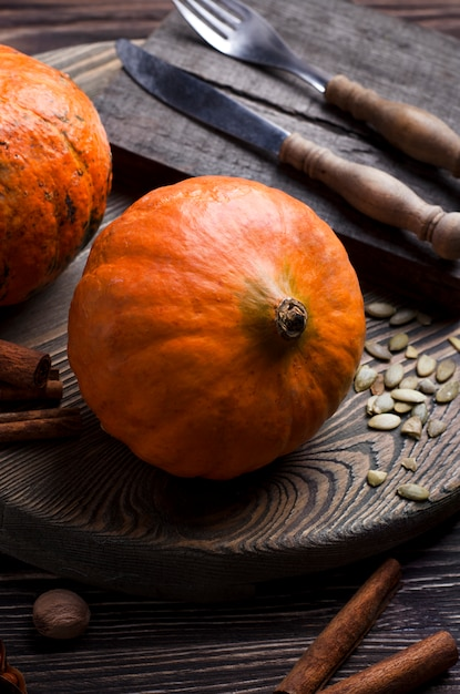 Close-up view of pumpkins, pumpkin seeds, spices and cutlery. rustic style, cooking process Premium Photo