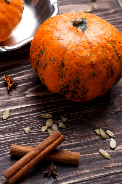 Close-up view of pumpkins, pumpkin seeds and spices. rustic style, autumn cooking concept Premium Photo
