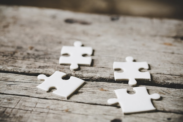 A close up view of several white jigsaw puzzle pieces Free Photo