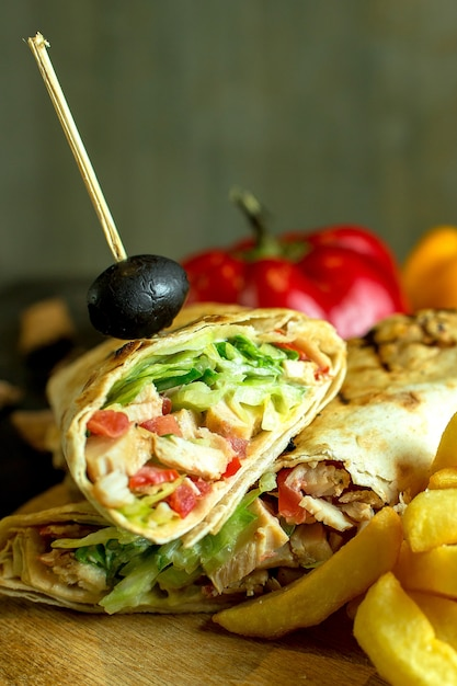 Close up view of shawarma sandwich with chicken meat cabbage carrots sauce green wrapped in lavash Free Photo