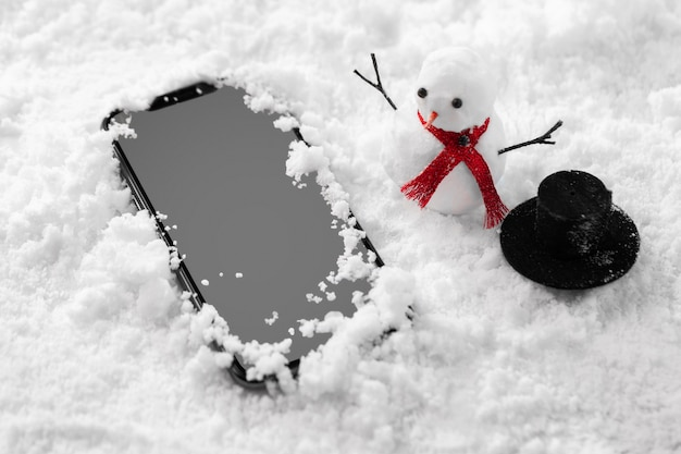 Close-up view of smartphone in snow Free Photo