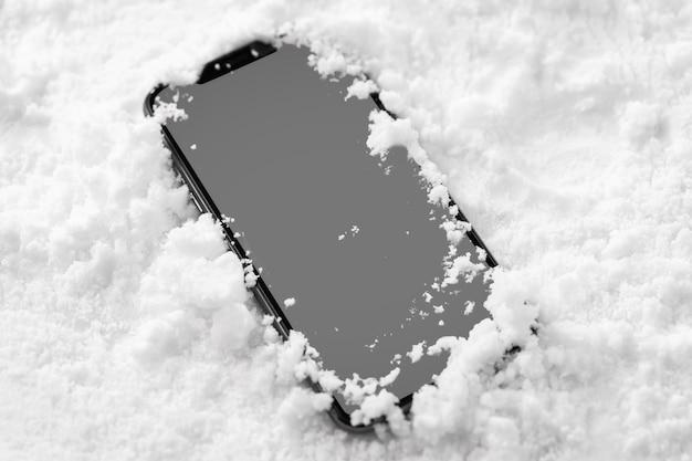 Vista ravvicinata di smartphone nella neve Foto Gratuite