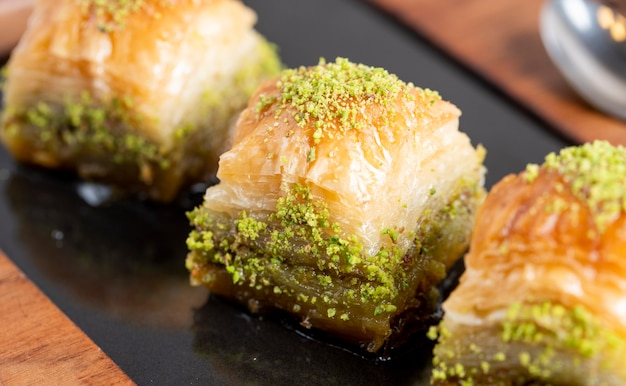 Close up view of traditional turkish baklava with pistachio on a black board Free Photo