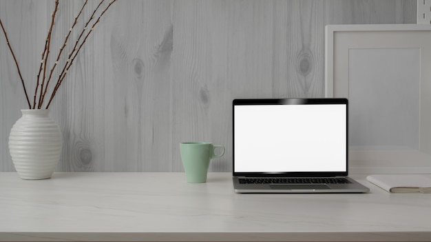 Close up view of trendy workspace with blank screen laptop on marble desk with white modern rustic wall Premium Photo