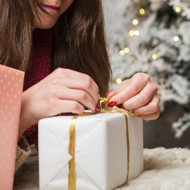 Close up view of woman opening present Free Photo