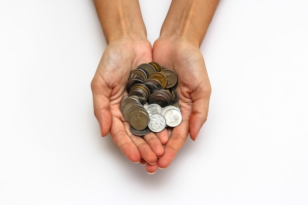 Close up view of woman's hands with indian rupees coins on white background. Premium Photo
