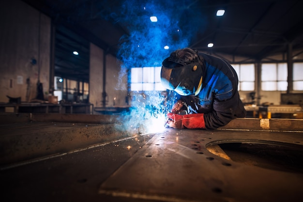 Close up view of worker welding metal construction in industrial workshop Free Photo