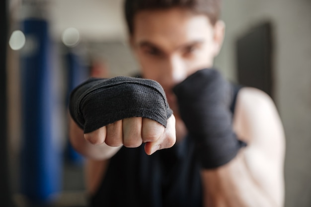 Close up  view of young boxer doing exercise in gym Free Photo