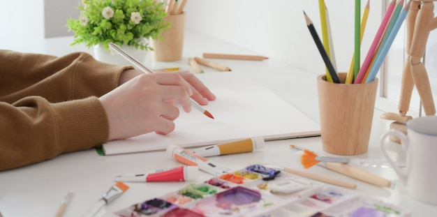 Close-up view of young female artist painting her project with water colour with painting brush Premium Photo