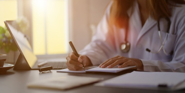 Close-up view of young female doctor writing medical charts with tablet in office room Premium Photo