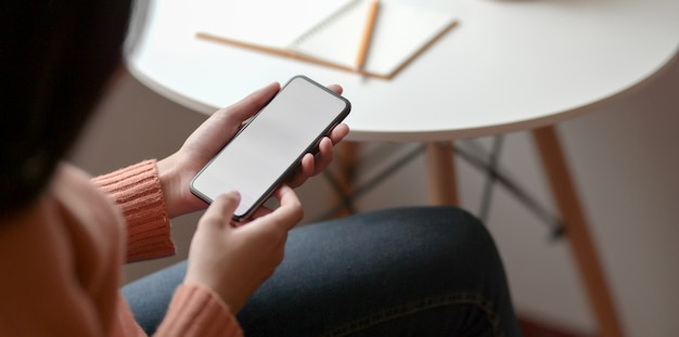 Close-up view of young female holding blank screen smartphone Premium Photo
