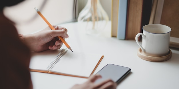Close-up view of young female writing her idea on notebook while touching her smartphone Premium Photo