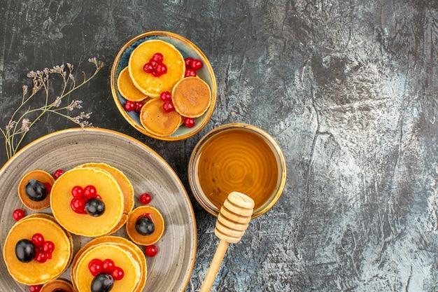 Vista ravvicinata di gustose frittelle su un piatto piccolo e grande con miele Foto Gratuite