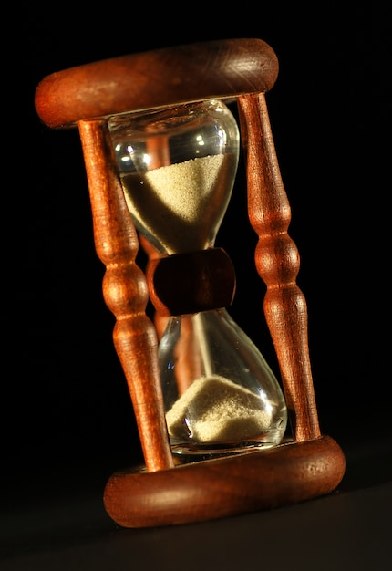 Close-up vintage hourglass with black background Free Photo