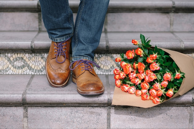 Close-up of vintage shoes with purple laces and a bouquet of roses Free Photo