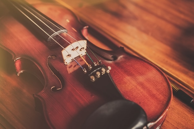 Close up of violin on wood background in vintage style. Premium Photo