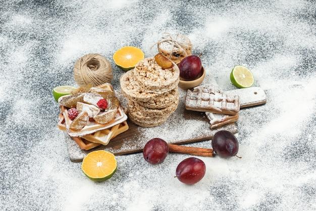 Крупным планом вафли и рисовые вафли с цитрусовыми, корицей и печеньем на темно-серой мраморной поверхности. горизонтальный Бесплатные Фотографии